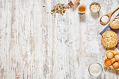 Set of fresh bread, wholegrain flour, olive oil, eggs in a carton tray, wooden spoon, grains and seeds over light wooden table.
