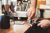 Barista tamping fresh coffee