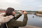 Female tourist taking photograph with mobile phone in Prague