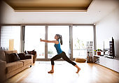 Young woman exercising at home, stretching legs and arms.