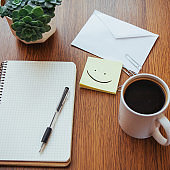 notepad and pen beside a cup of coffee on a wooden table outdoors at a cafe.