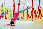 young woman making antigravity yoga exercises