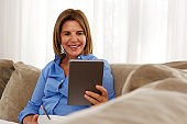 woman relaxing at home with breakfast and digital tablet
