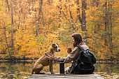Female tourist sit with dog near lake and enjoy beautiful autumn view drinking cup of coffee