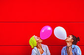 Two young female friends having fun, blowing up balloons in front of the red wall