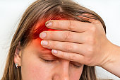 Woman with headache is holding her aching forehead