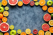 Citrus fruits sliced mix frame flat lay on blue concrete background blank copy design space