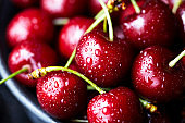 Sweet cherry close-up macro, lies on a plate in droplets of water. Antioxidant, natural, organic berry. Macro background