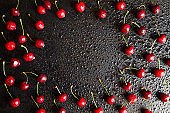 Cherry background on a black table with drops of water on the surface of the berry and background. Copy space for text. View from above. Antioxidant, natural, vitamin, organic berry.