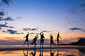group of happy people jumping on the beach at sunset