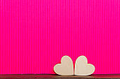 Hearts of wood on the pink corrugated background. Valentine's day background.