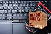 Special delivery of Black Friday online orders with carton box in shopping cart on laptop keyboard