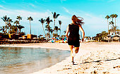 Rear view of female athlete running fast on a beach in a tropical climate