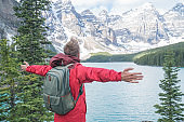 Young man hiker arms outstretched at mountain lake