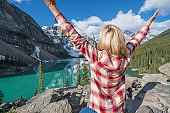 Young woman hiker arms outstretched at mountain lake