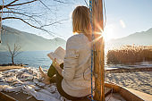 Young woman relaxing by the lake reading book