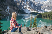 Young woman hiker on rock above mountain lake