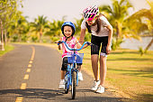 Mother teaching her daughter cycling