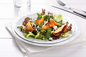Fresh mixed salad on white. Lettuce and arugula leaves with grilled peach and blue cheese.  Healthy food.