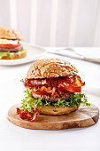 Close-up of beef burger on white background. Hamburger - bun, grilled meat burger, lettuce, tomato and bacon.