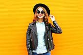 Fashion smiling woman in black rock jacket, hat over colorful orange background