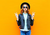 Fashion woman blowing lips in black rock jacket, hat over colorful orange background