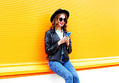 Fashion smiling woman is using smartphone in black rock jacket, hat over colorful orange background