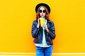 Fashion woman drinks fruit juice in black rock jacket in the city on a colorful orange background