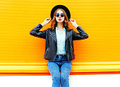 Fashion woman in black rock jacket sitting in the city on a colorful orange background