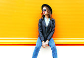 Fashion woman in black rock jacket sitting in the city on a orange background