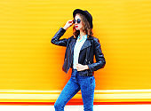 Fashion woman in black rock jacket, hat over colorful orange background, looks in profile