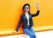 Fashion woman is taking a picture on a smartphone on colorful orange background