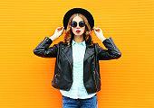 Fashion pretty woman posing in black rock jacket, hat on a colorful orange background