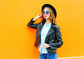 Fashion woman in black rock jacket, hat on a colorful orange background, looks in profile