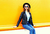 Fashion woman in black rock jacket sitting in the city over colorful orange background