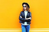 Fashion pretty woman in black rock jacket, hat on a colorful orange background, looks in profile