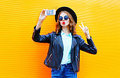 Fashion woman is taking a picture on a smartphone in black rock jacket on colorful orange background