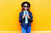 Fashion woman is using smartphone in black rock jacket on colorful orange background