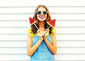 Portrait happy smiling woman with a two slice of watermelon in the form of ice cream over a white background