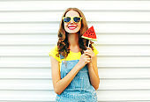 Happy smiling woman with a slice of watermelon in the form of ice cream over a white background