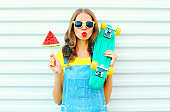 Fashion pretty woman with slice watermelon ice cream skateboard on a white background