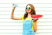 Fashion pretty girl with a watermelon taking picture selfie on the smartphone over a white background
