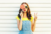 Fashion portrait woman holding a lollipops and blowing her lips over a white background