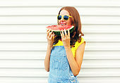 Fashion portrait happy young woman is holding slice of watermelon in hands and eating over a white background