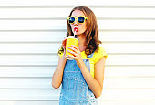 Fashion portrait pretty woman drinks a juice from cup over a white background