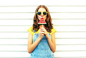 Fashion pretty woman eating a slice of watermelon in the form of ice cream on a white background