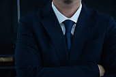 Part of man body side folded his arms in black suit on black background, business concept .
