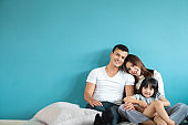 Portrait happy Asian family over blue background