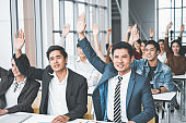 Group of business people raise hands up to agree with speaker in the meeting room
