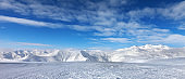 Ski slope, snow mountains and blue sky with clouds
